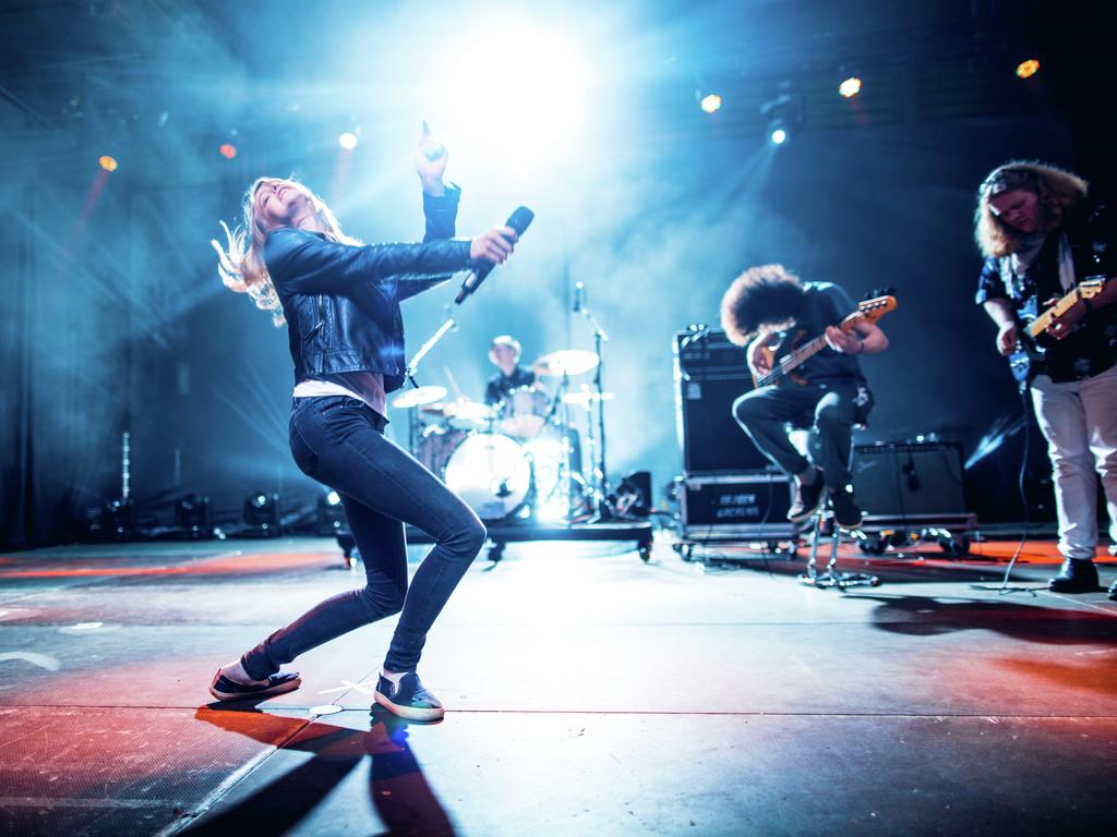 Foto frå UKM-festivalen i 2017. Vi ser eit rockeband på scena, med dansande vokalist og gitaristar som rockar med.