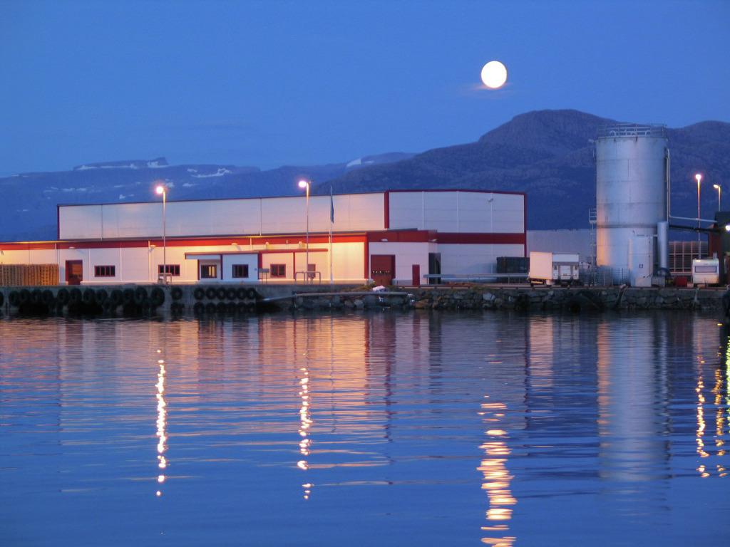 Firkanta kvit bygning med raude lister ved ei hamn. Månen lyser ned i fjorden ved skumringa. Foto: Sogn og Fjordane fylkeskommune