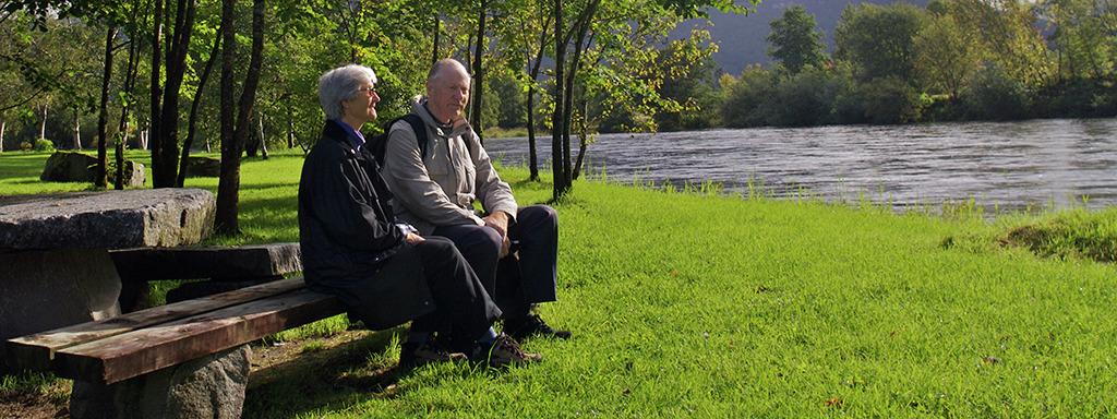 Eldre par som sit på benk ved ei elv. Foto: Oskar Andersen