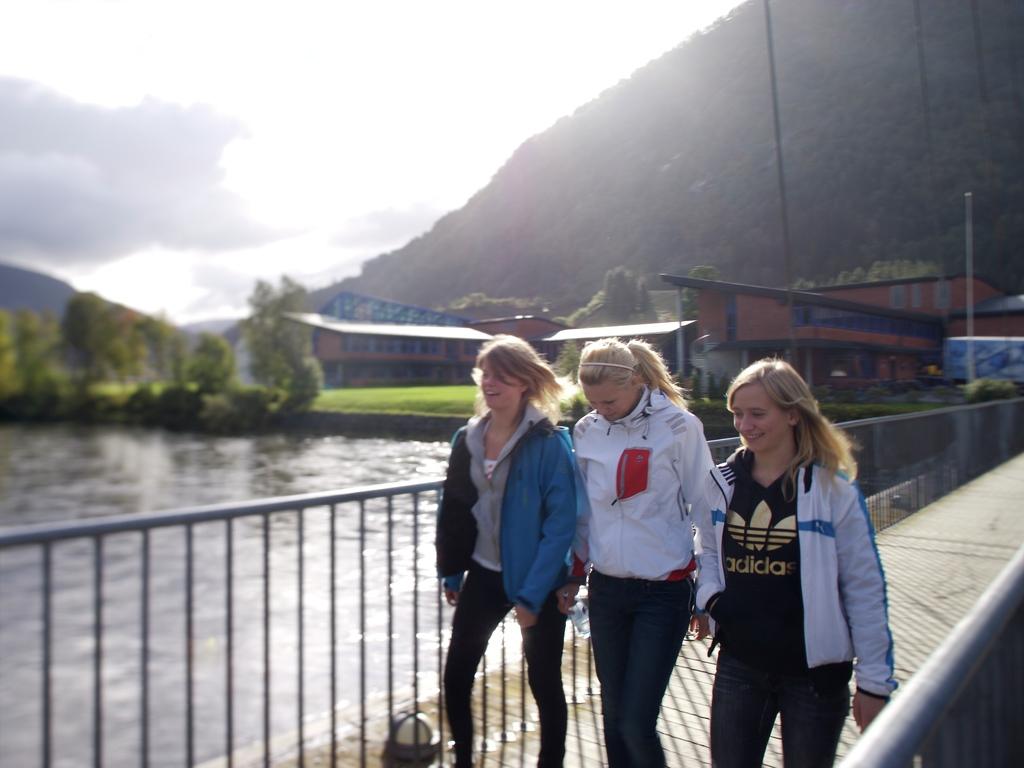 Foto av tre jenter på veg over ei bru i Førde. Dei smiler og ler, det er sommar, og i bakgrunnen ser vi Hafstad vidaregåande skule.