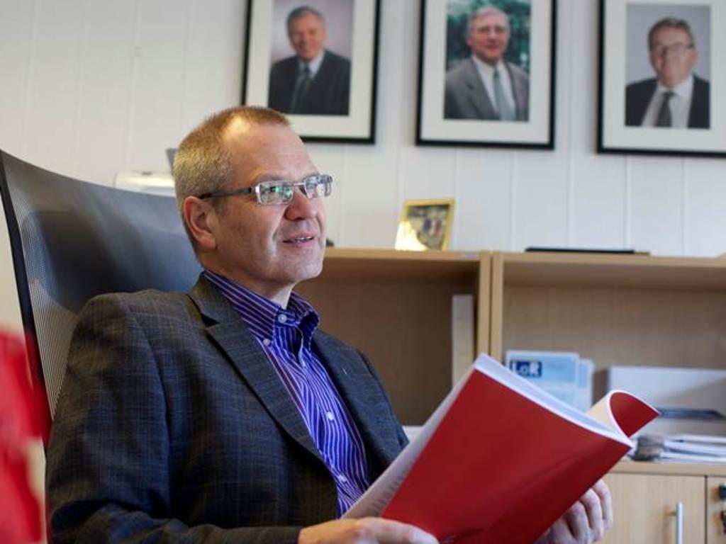 Foto av fylkesrådmann Tore Eriksen på kontoret. Han blar i eit dokument, og på veggen bak han ser vi tre tidlegare fylkesrådmenn.