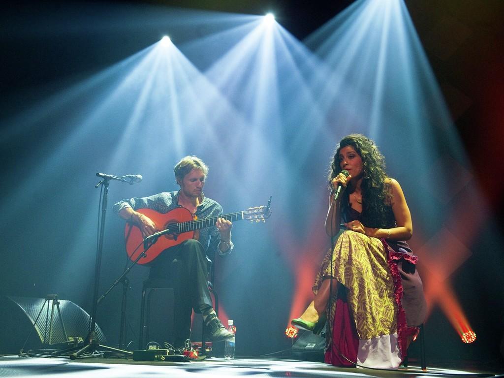Foto frå ein konsert på Førdefestivalen, ein mann og ei kvinne på ein mørk scne med litt blått lys. Han spelar gitar og ho syng.