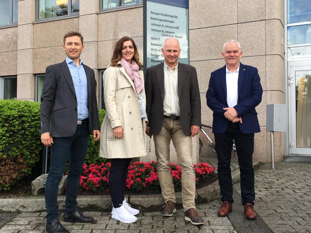 Foto av dei fire nye kompetansemeklarane i VRI4-prosjektet til fylkeskommunen. Det er tre menn og ei kvinne som står framfor lokala til Forskingsrådet i Oslo.