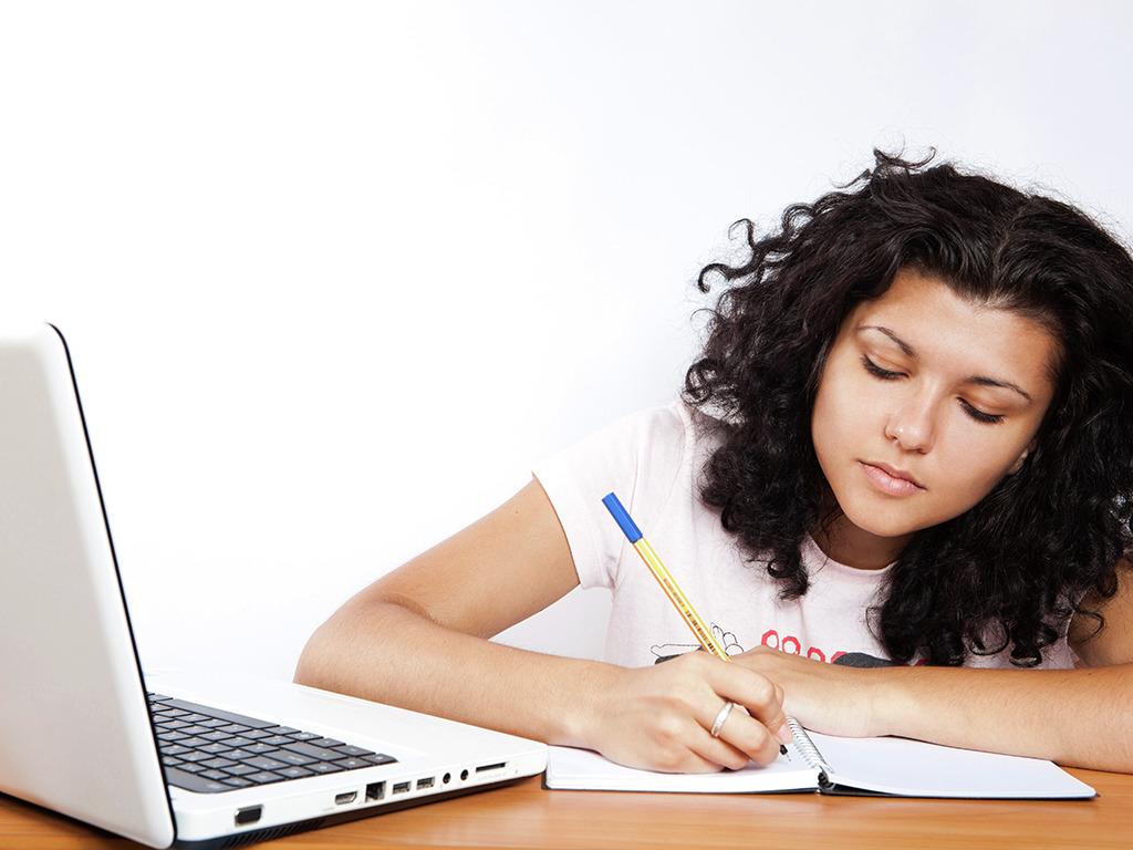 Jente med mørkt og krøllete hår som sit og skriv i ei bok med ein bærbar PC framfor seg. Foto: CollegeDegrees360/flickr.com