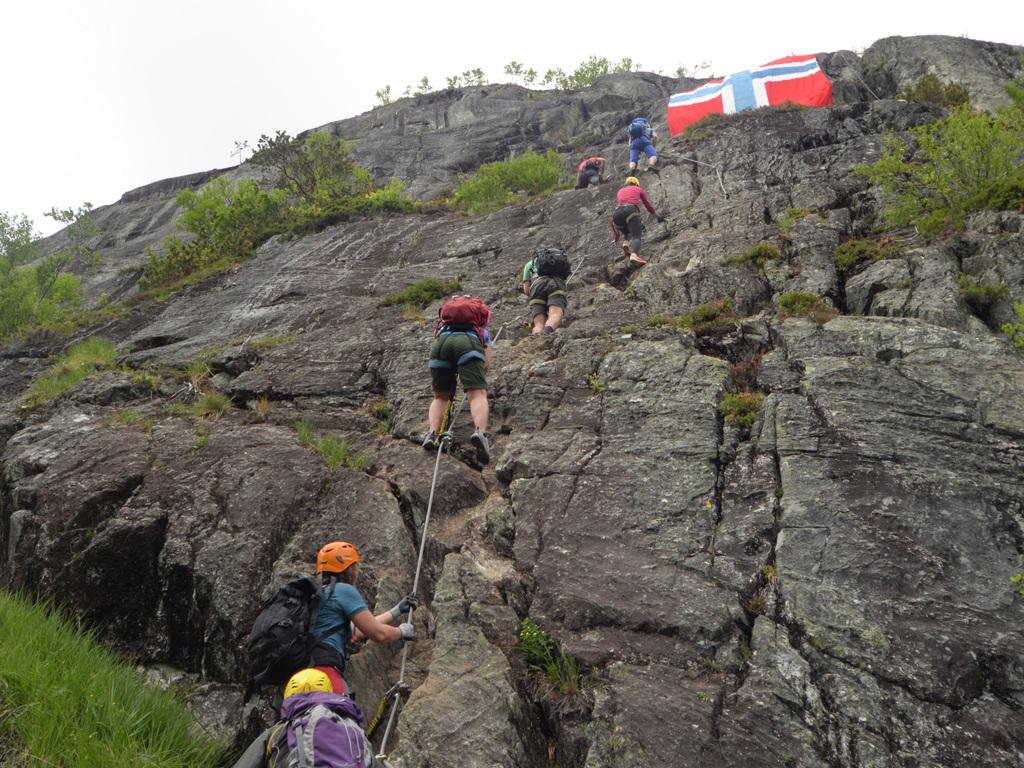 Foto frå Via Ferrata i Loen. Vi ser ein gjeng med klatrarar bakfrå på veg oppover bratt fjell. På noppen er det eit norsk flagg langs fjellsida.