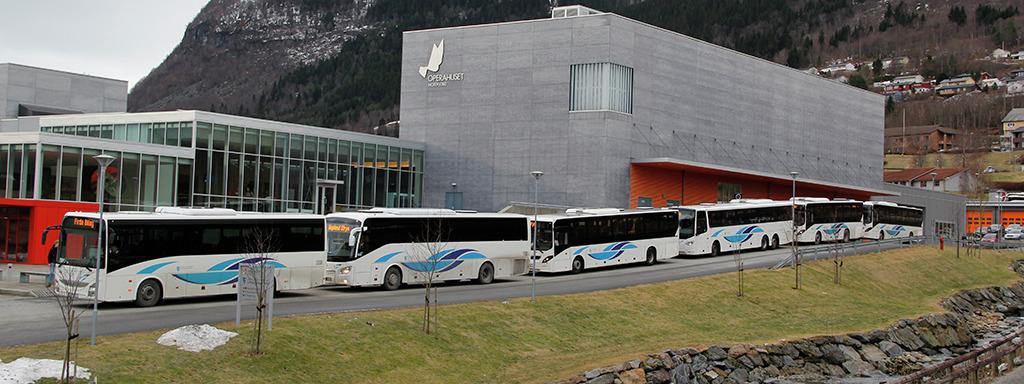 Seks bussar på rad utanfor Operahuset i Nordfjord. Alle bussane har Kringom-logo. Foto.