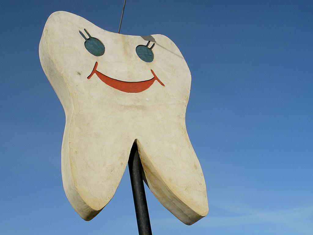 Foto av eit betongskilt forma som ei smilande tann. Bakgrunnen er blå himmel.