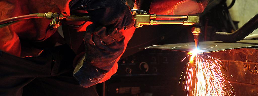 Mann med beskyttelsesutstyr som sveisar. Foto: Michael Russell/U.S Navy