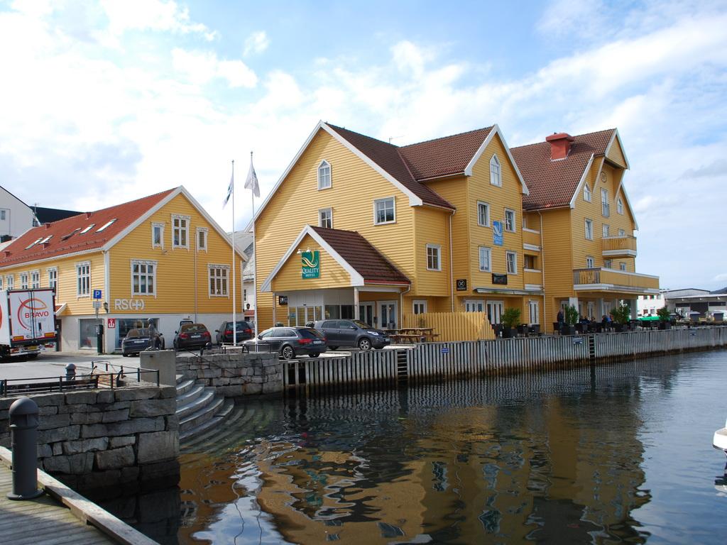 Foto av det gule bygget som rommar Quality Hotel Florø. Hotellet ligg heilt nede ved sjøen, og vi ser sjøen i framgrunnen. Det er overskya og litt blå himmel.