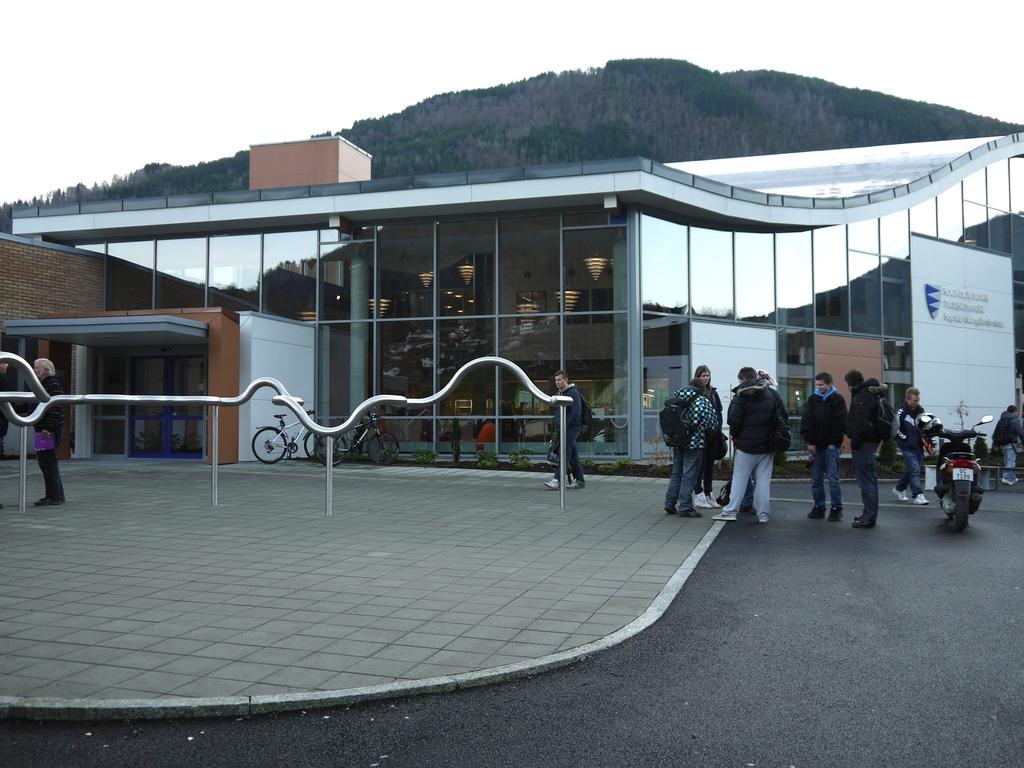 Foto av inngangspartiet ved Sogndal vidaregåande skule. Det er samla nokre elevar i ei klynge til høgre i biletet, og til venstre står to personar og snakkar.