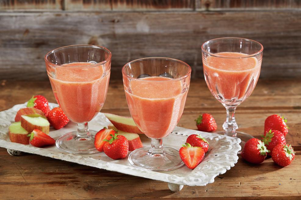 Tre glass jordbærsmoothie på hvitt brett på trebord
