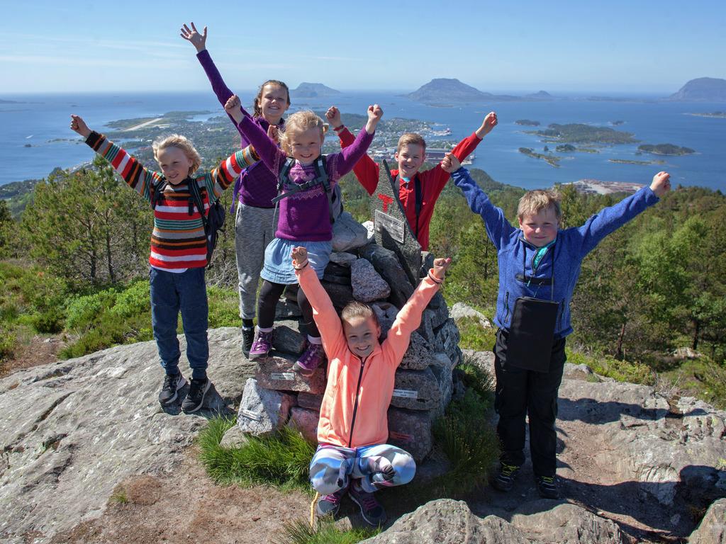 Foto av ungar som held hendene i vêret på ein topp med utsikt over Florø.