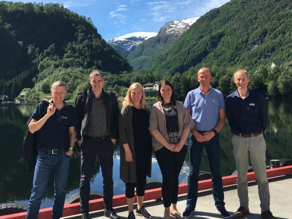 Foto frå kaien i Hyen, med deltakarane på eit møte oppstilte med fjell og blå himmel i bakgrunnen. Det er fire menn og to kvinner.