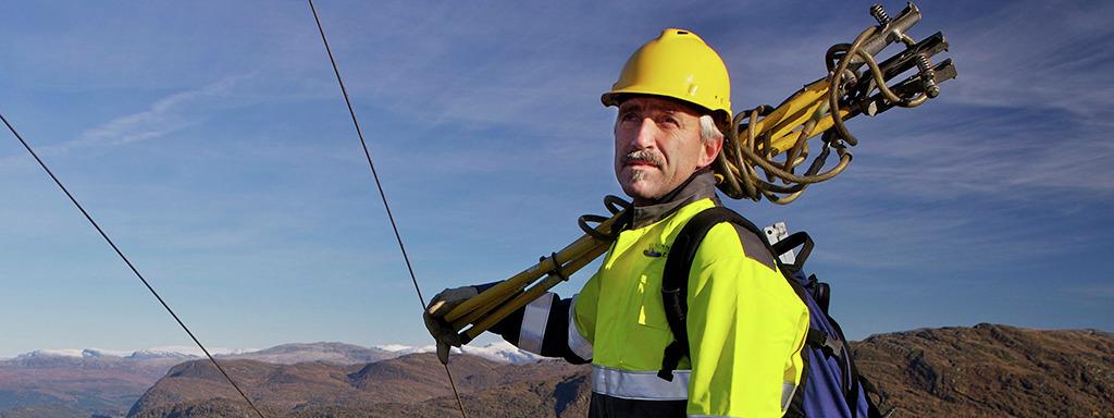 Energimontør med gul hjelm på toppen av Hafstadfjellet. Foto: Oskar Andersen