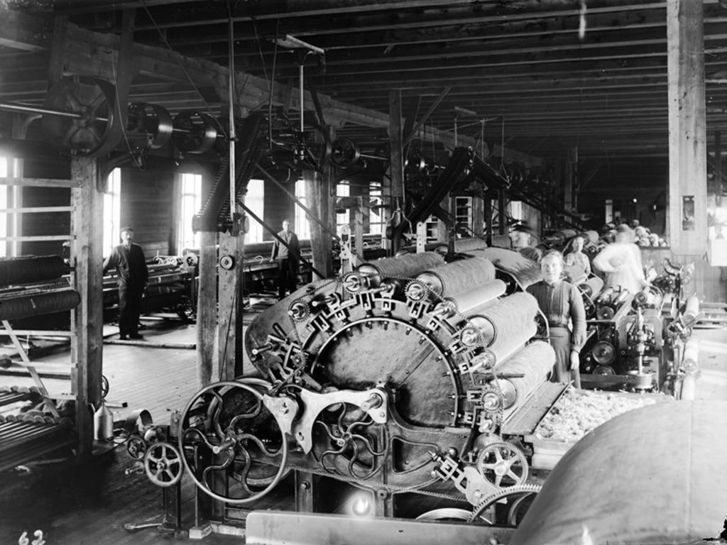 Bilete i svart-kvitt av maskiner og arbeidarar inne på ullvarefabrikken.