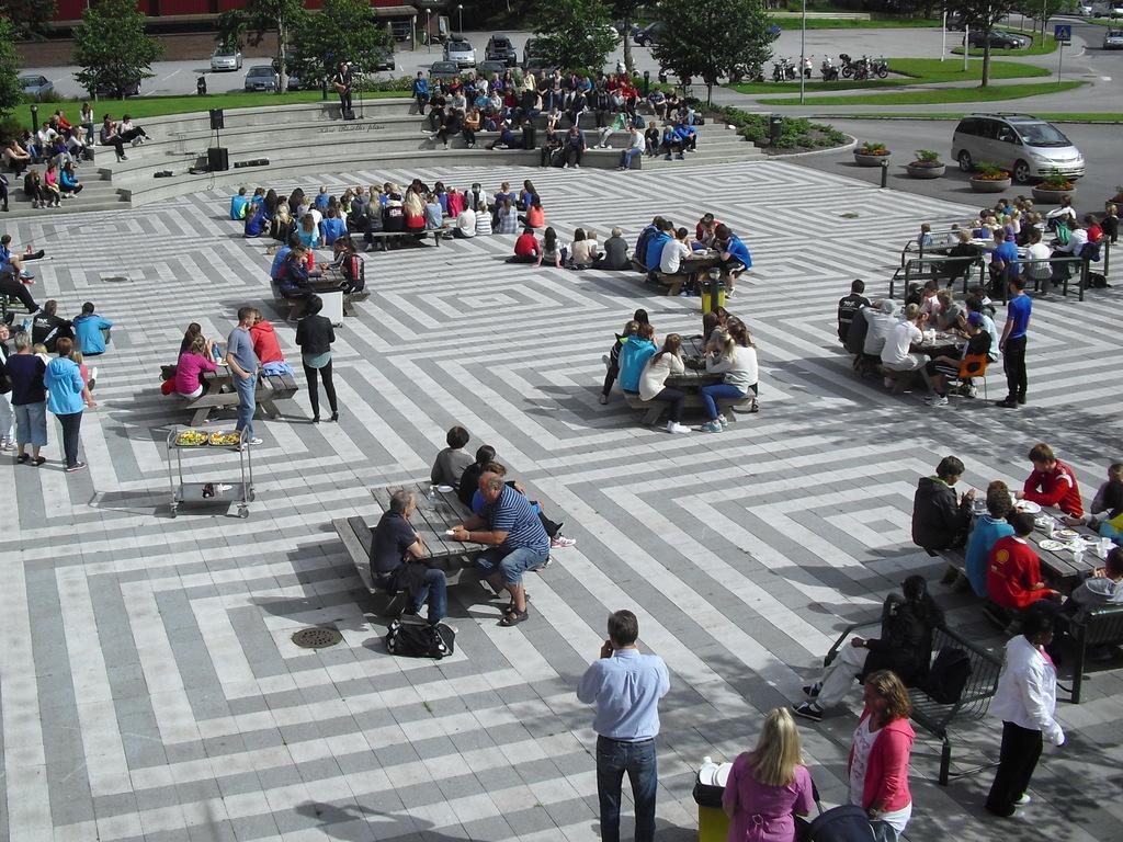 Oversiktsbilete over plassen utanfor Stryn vidaregåande skule. Foto er teke ovanfrå, og det er mange elevar samla i klynger på plassen.