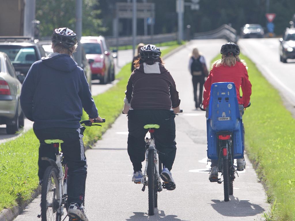 Tre menneske på sykkel som alle har hjelm. Den eine sykkelen har barnesete på bagasjebrettet. Vi ser alle bakfra, syklande på ein gangveg. Foto.