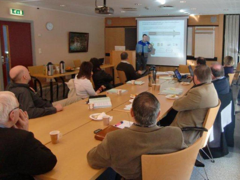 Møte i hovudutvalet for Plan og Næring i Årdal. Hovudutvalet sit rundt bordet og ser på powerpoint-presentasjon på projektor.