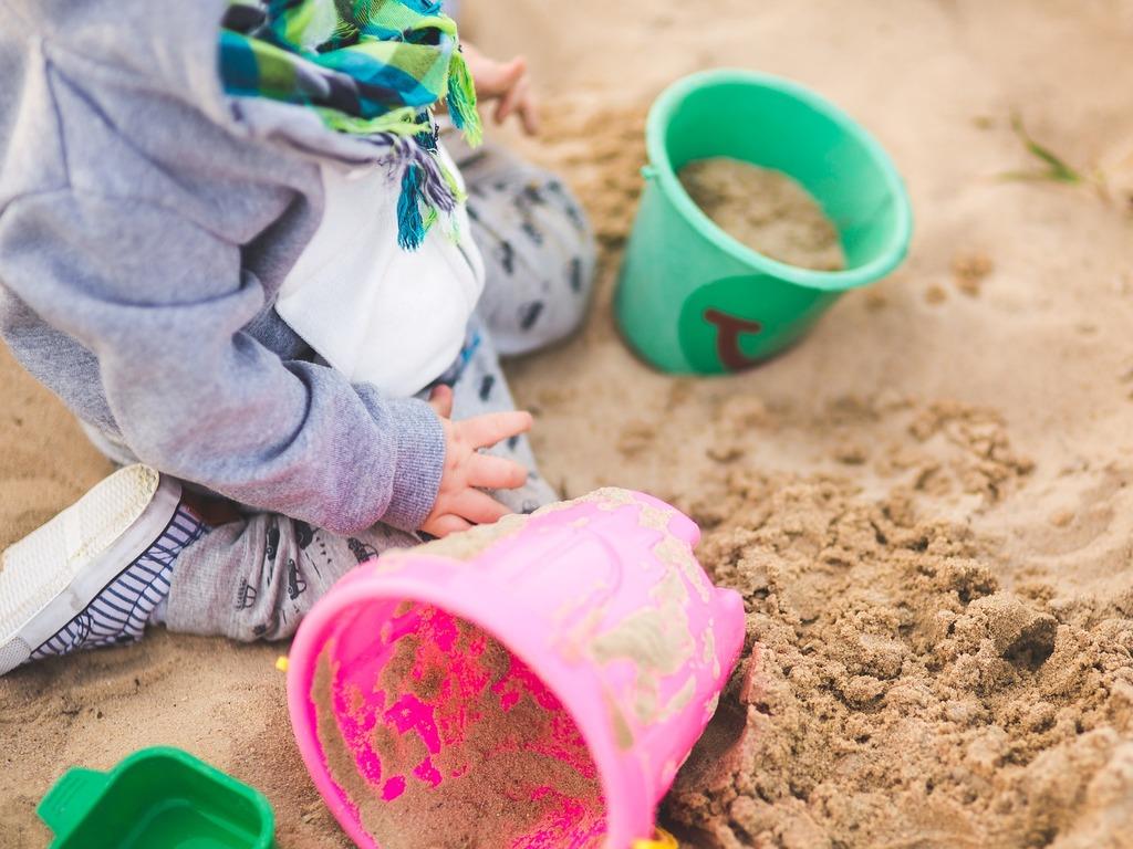 Foto av ein liten unge, ca. eitt år, i ein sandkasse. Vi ser kroppen, men ikkje hovudet, og han/ho er kledd i grå joggedress. Det ligg ei grøn og ei rosa bøtte i sanden, i tillegg til ei anna grøn leike.