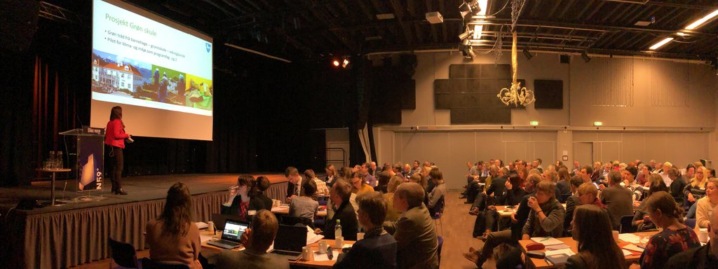 Foto frå konferansesal med mange folk samla rundt små langbord. På scena står ei kvinne i svart bukse og raud jakke. Presentasjonen ho har på skjermen har teksten Grøn skule