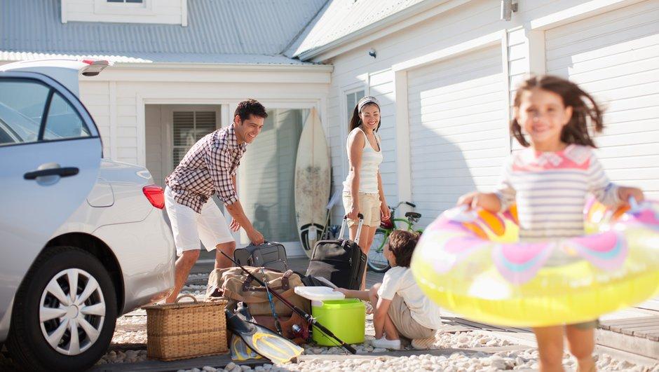 Perhe pakkaa tavaroita pois autosta talon pihassa