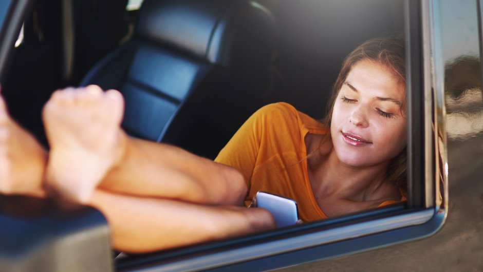 en kvinna  sitter i bilen och bläddrar i sin telefon