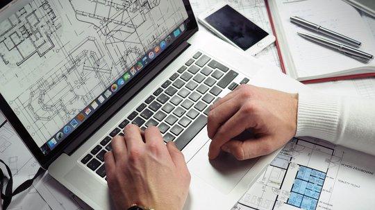 Arkitekt som tegner på laptop