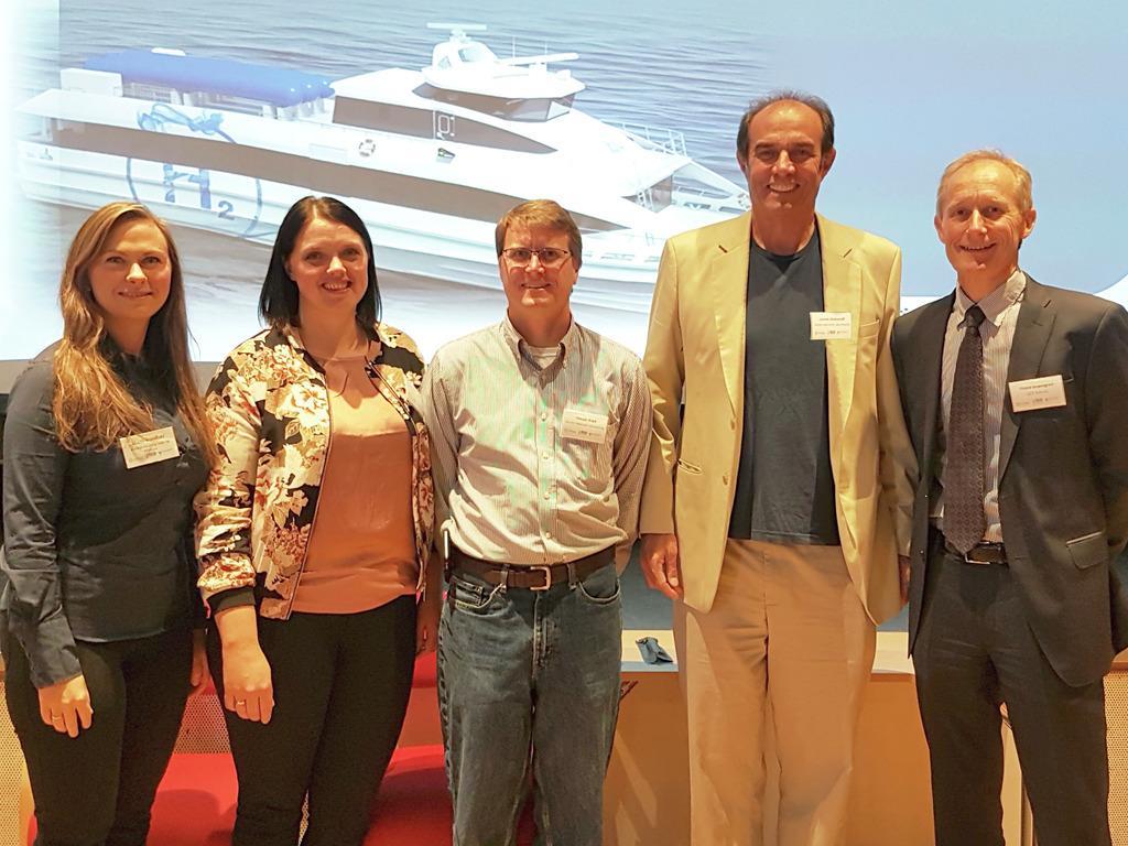 Foto av fem personar, tre menn og to kvinner, som står framfor eit lysbilete av ein hurtigbåt med skrifta H2 på sida av båten. Det er frå den internasjonale hydrogenkonferansen i Florø i september 2017.