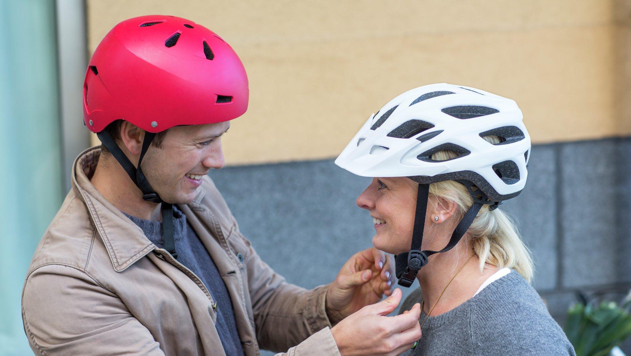 Mies auttaa naista pyöräilykypärän kanssa