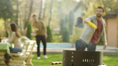 Kastar friesbee i trädgården