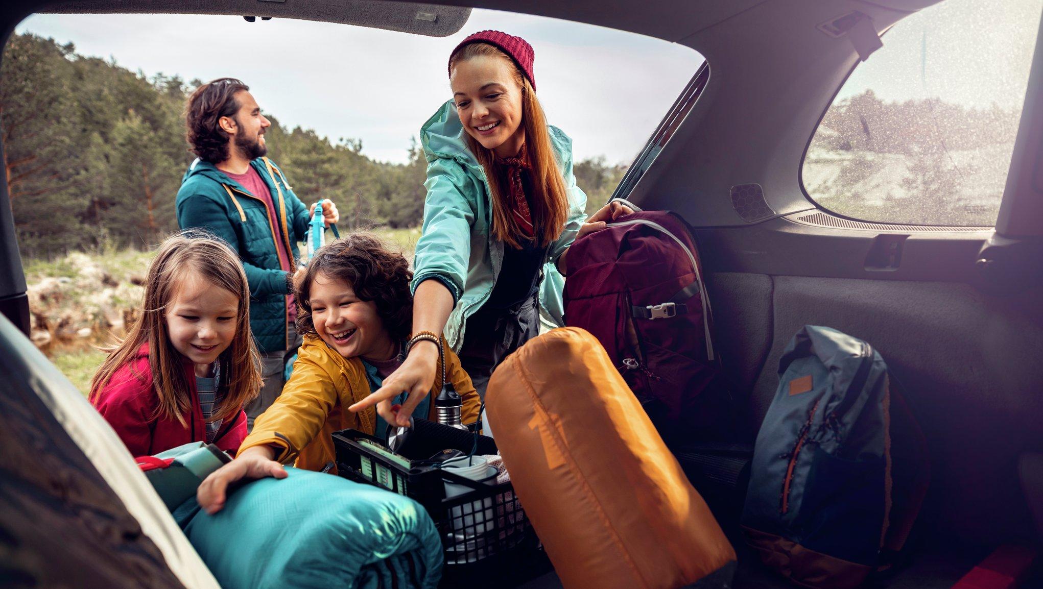 Perhe ottaa makuupusseja ulos autosta