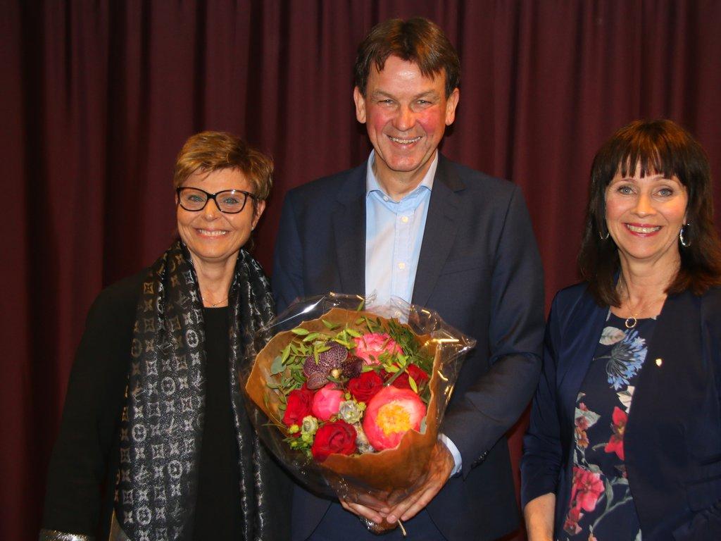 Rune Haugsdal med fylkesordførarane Anne Gine Hestetun og Jenny Følling. Haugsdal smiler breidt med ein stor bukett blomar i hendene.