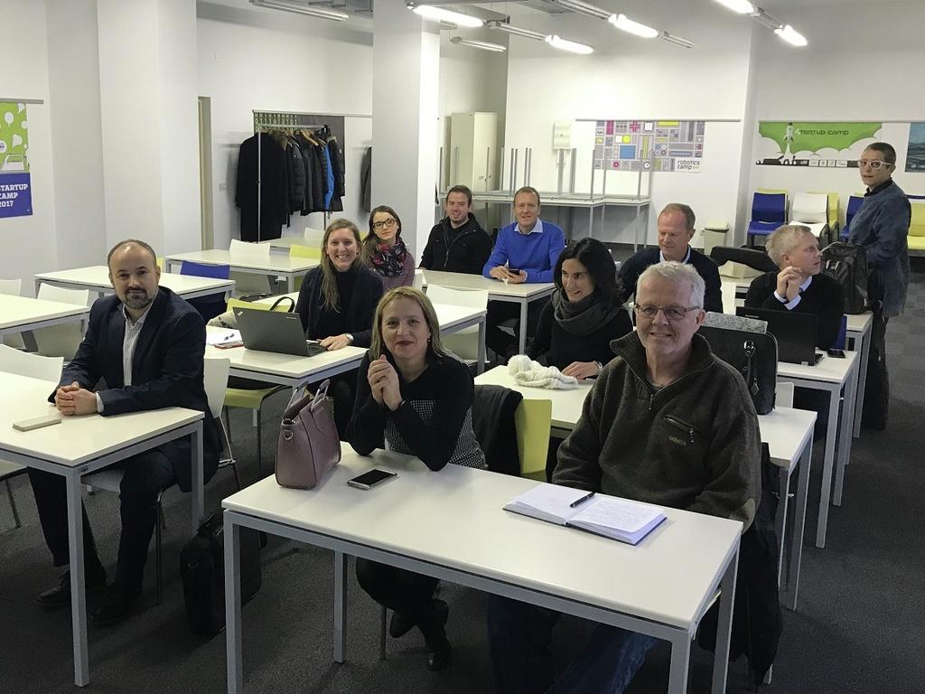 Foto av elleve personar i eit klasserom med kvite veggar og kvite pultar.