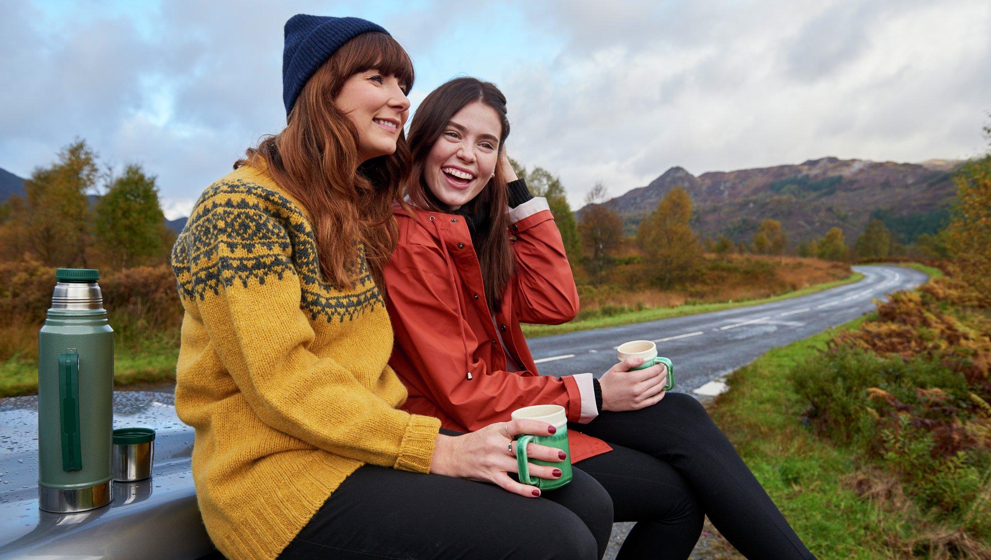Kaksi naista istuu penkillä valtatien varrella