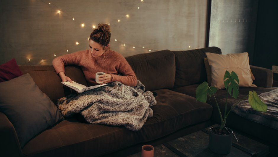woman sitting and reading in her couch.