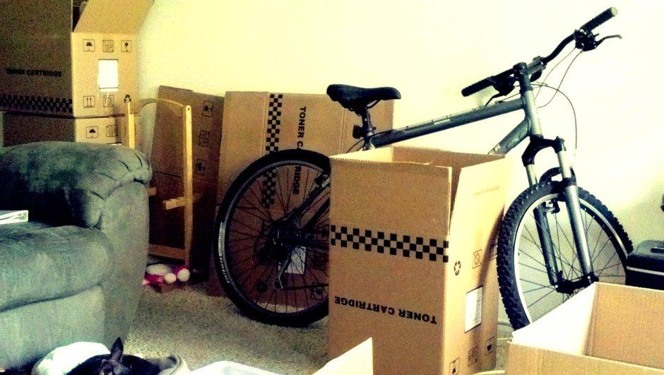 Flyttekasser og cykel står klar til flytning.