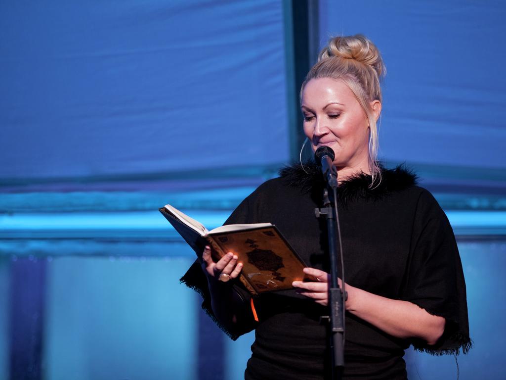 Foto av Sigrid Moldestad som les frå ei bok i ein mikrofon. Ho er kledd i svart, og det er blått lys i rommet rundt ho.