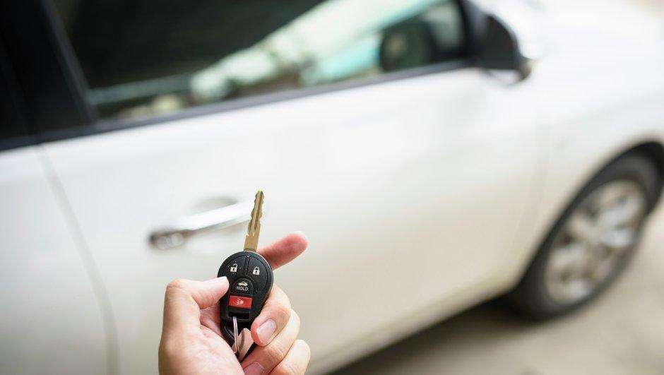 En hvid bil og en hånd med en bilnøgle.