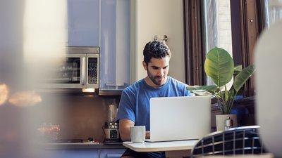 Mies työskentelee tietokoneella