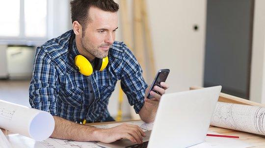 Byggarbeider ved skrivebord med mobil og pc