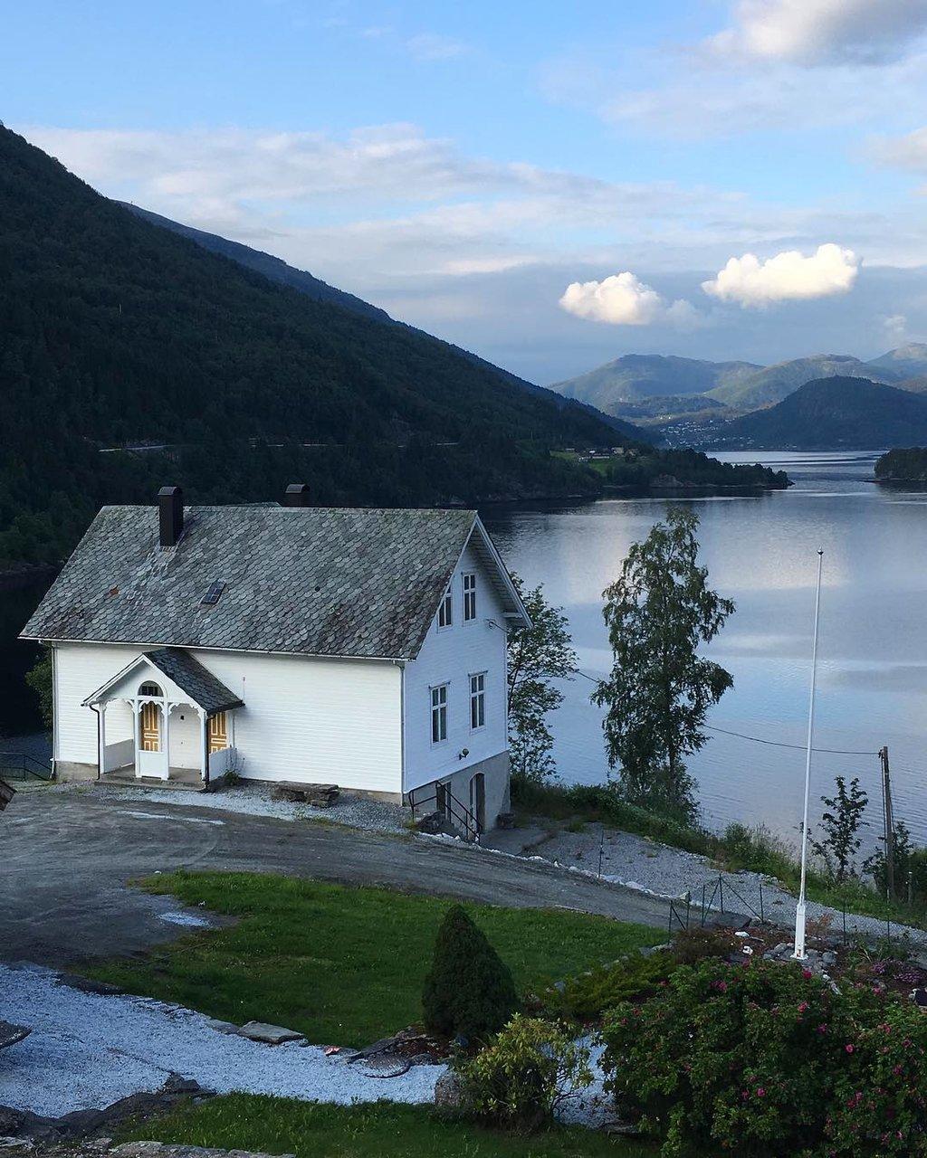 Bilete av kvitt skulehus med fjord og fjell i bakgrunnen.