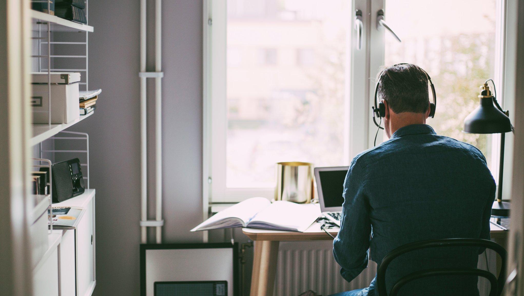 Mies istuu kannettavan tietokoneen edessä kotona