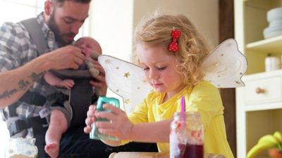 barn leker och pappa matar syskon