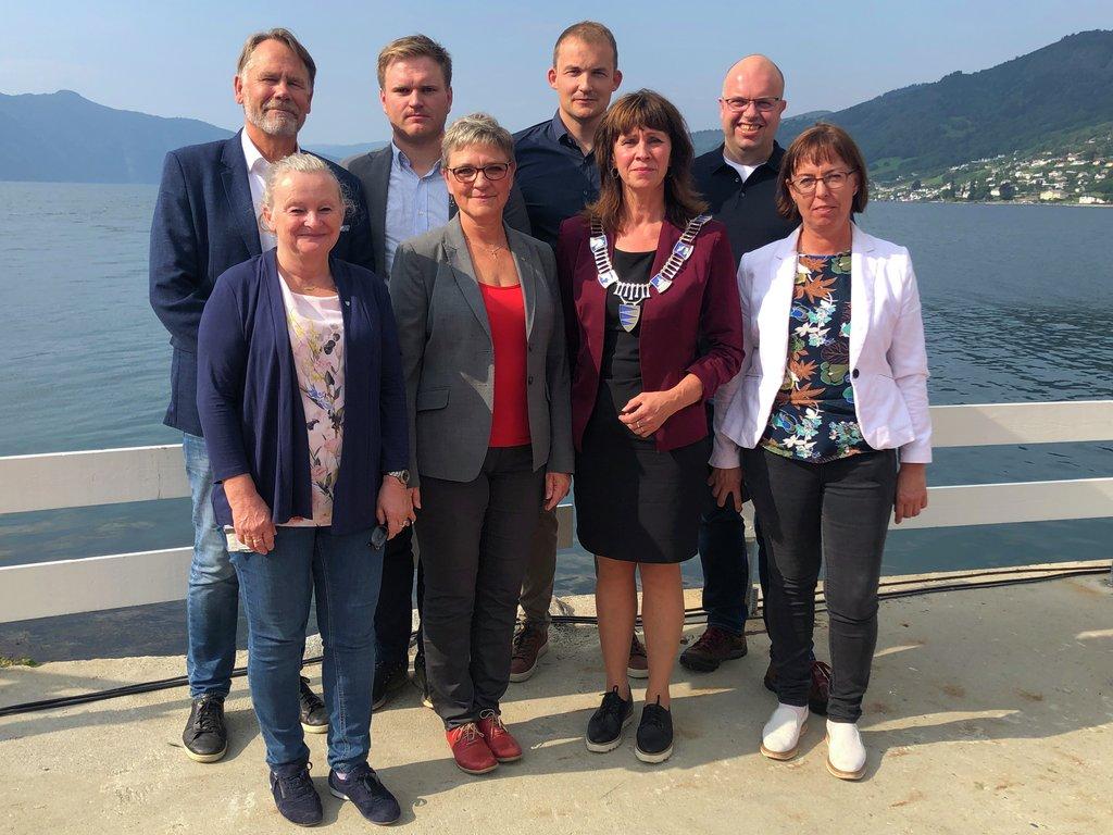 Foto av åtte av politikarane fylkesutvalet, teke ved sjøen på Leikanger.
