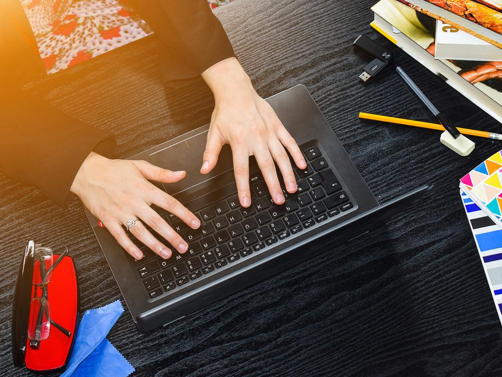 Illustrasjonsfoto av ein person som sit og jobbar med ein svart pc. Vi ser berre hendene til personen, og biletet er teke ovanfrå. Rundt pc-en ligg det briller, blyant, penn og diverse bøker.