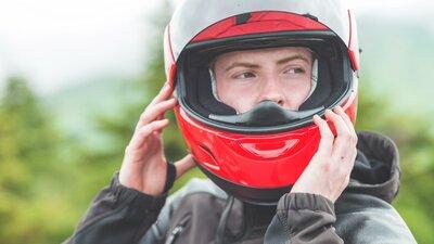 Mies laittaa punaista moottoripyöräkypärää päähänsä