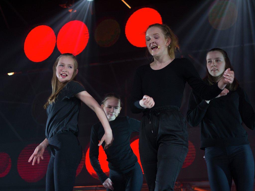 Fire jenter i svart står p åscena og dansar og syng