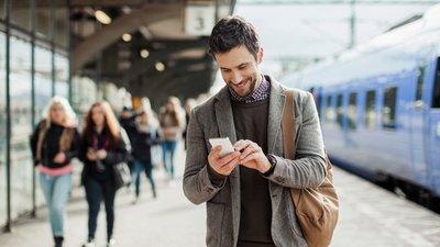 Mies selaa älypuhelinta juna-asemalla