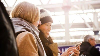 Kaksi naista katsoo kännykkää junalaiturilla