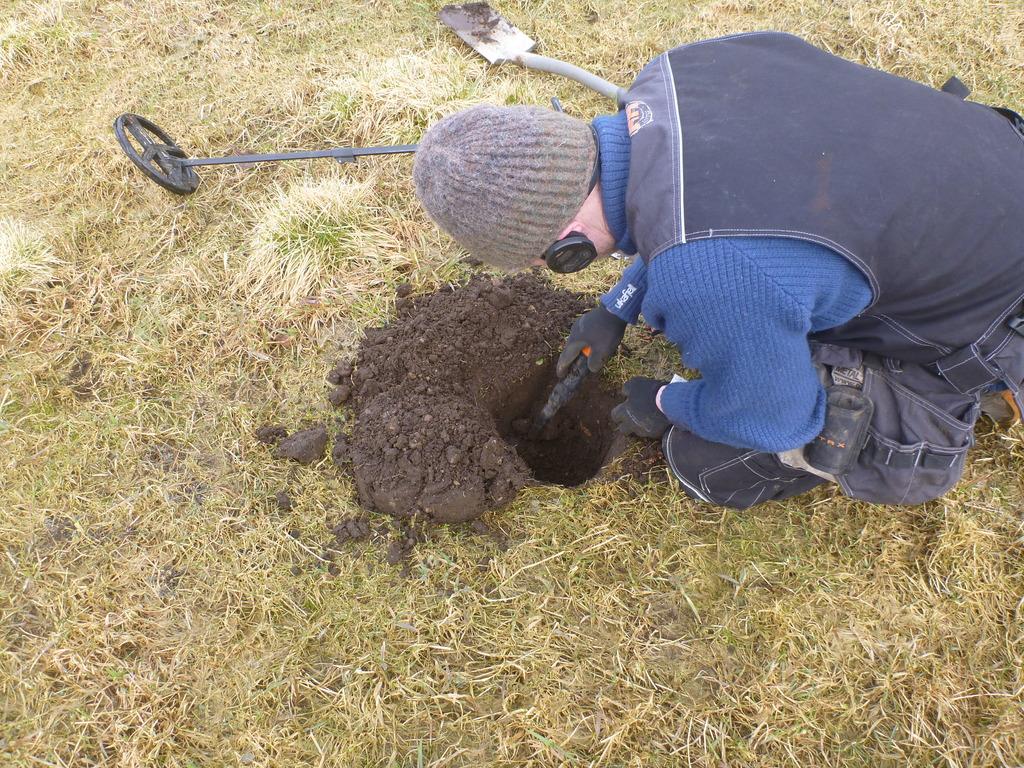 Foto av ein som sit bøygd over eit hol i marka og driv med metallsøking. Han har på seg blå arbeidsklede og ei grå lue. Ved sidan av han ligg ein metallsøkar og ein spade.